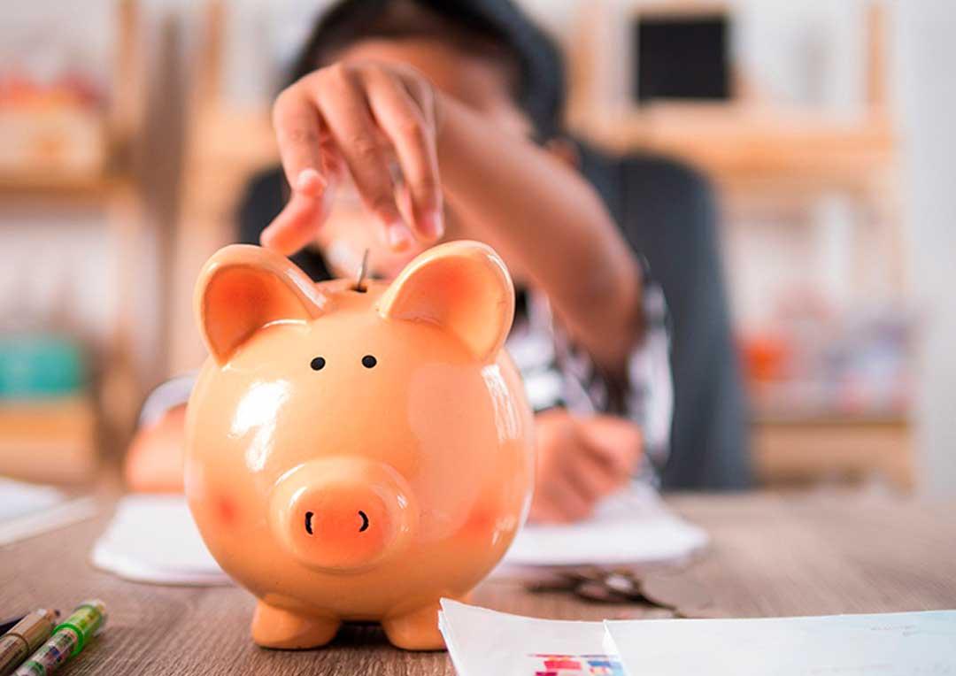 criança colocando moeda em cofrinho em formato de porquinho