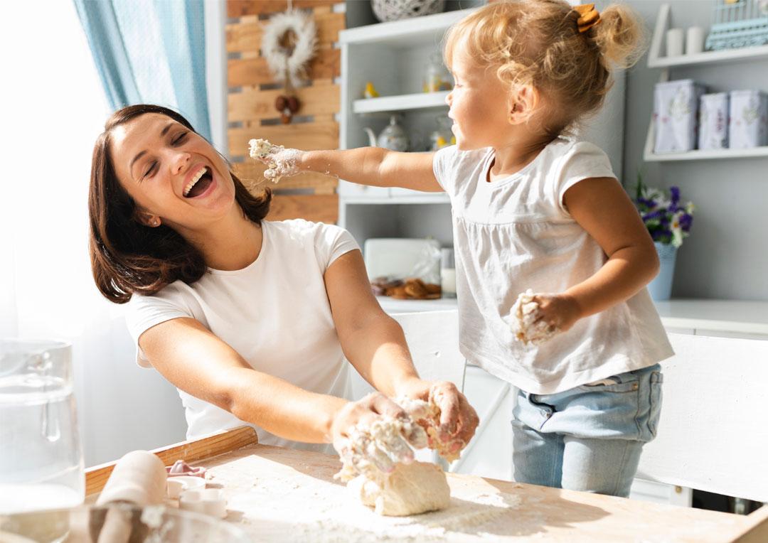 mãe e filha brincando na cozinha com receita culinária