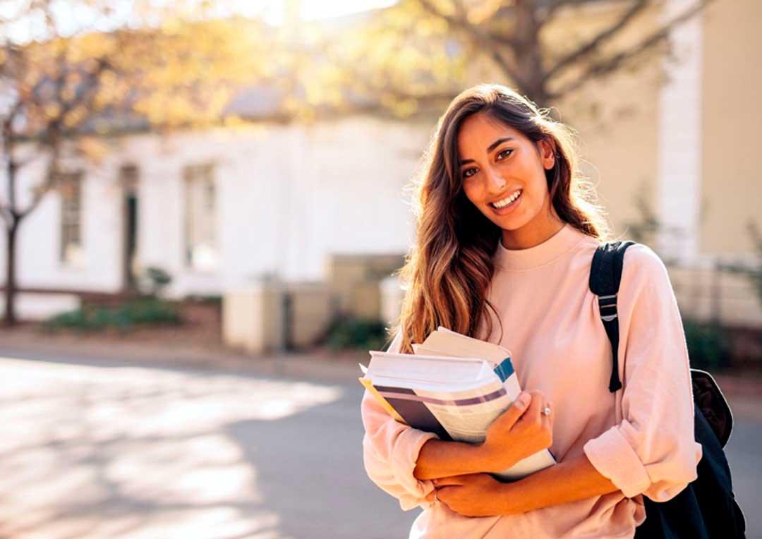 aluna adolescente segurando livros e cadernos