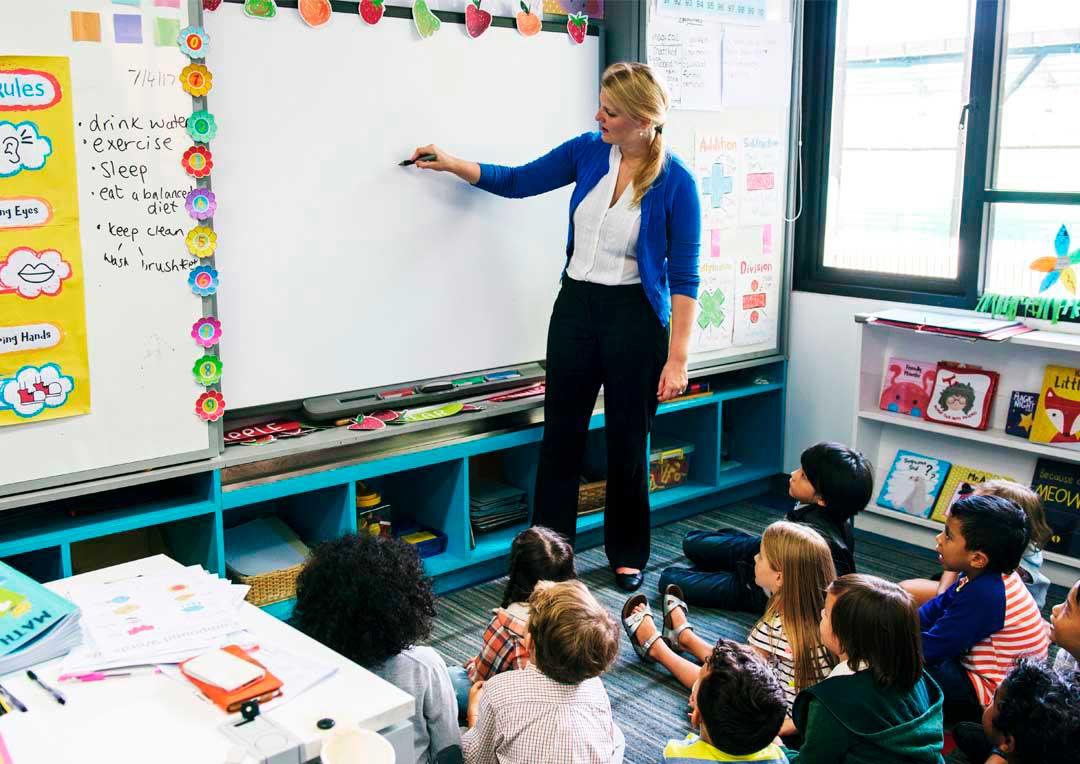 professora escrevendo na lousa e alunos assistindo a aula