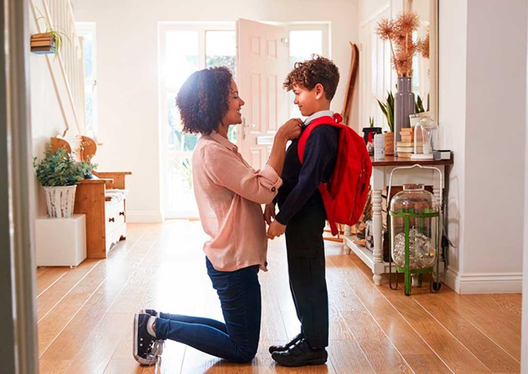 mãe de joelho arrumando a blusa do filho com mochila de escola
