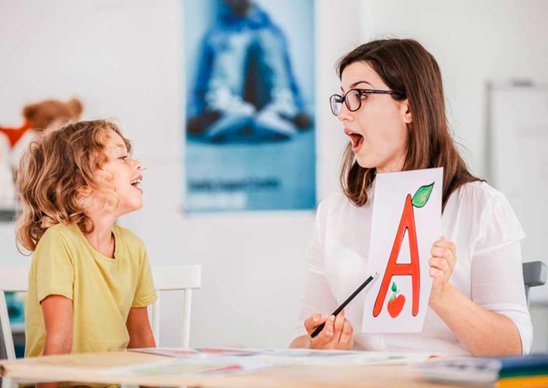 professora com uma cartaz com a letra e ensinando um aluno menino