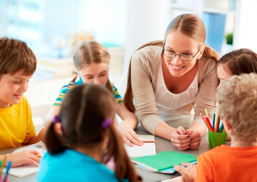 professora sorrindo com grupo de alunos e estudando