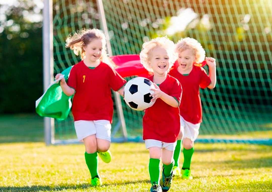 três crianças brincando juntas com uma bola